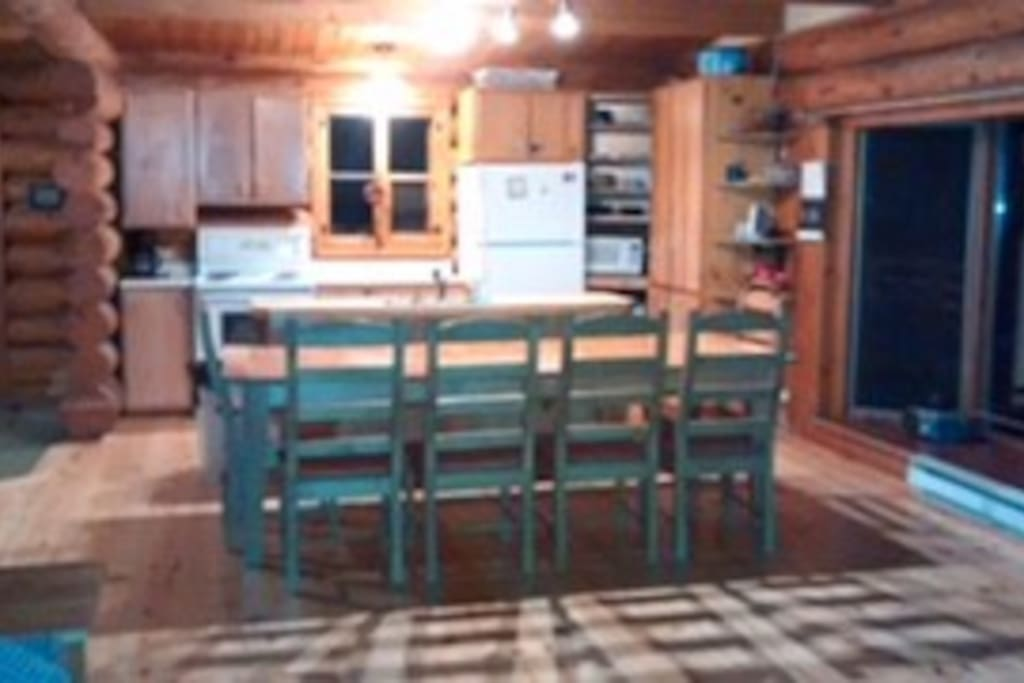 A full kitchen with all appliances and s large dining table