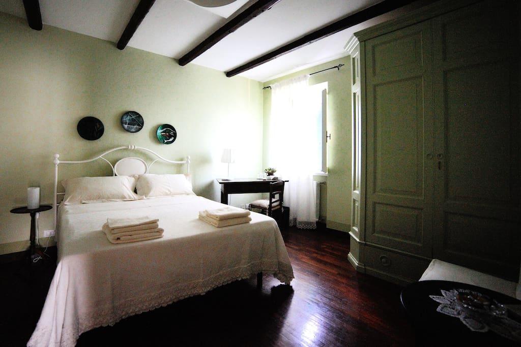 camera verde con letto matrimoniale e letto singolo.