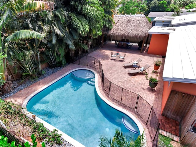 This 3BR home features a lushly landscaped pool area with tiki hut and outdoor dining area.
