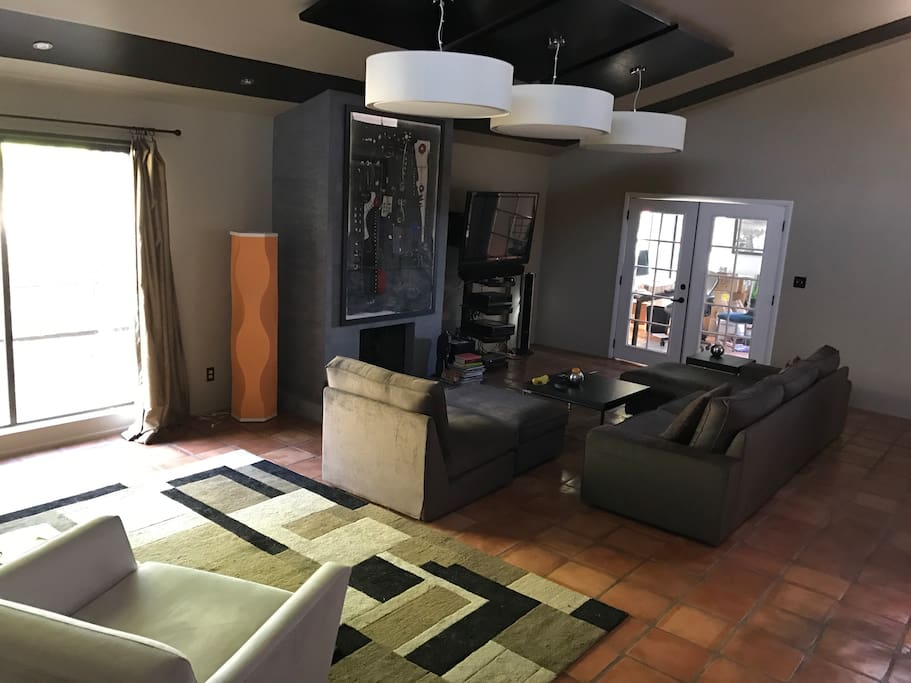 Large living room with large screen TV, cable, wireless and a workspace desk in the office area.