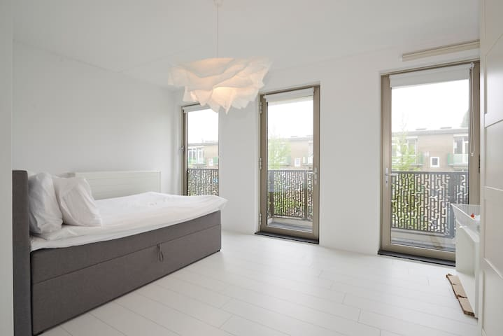 The bedroom has large windows,