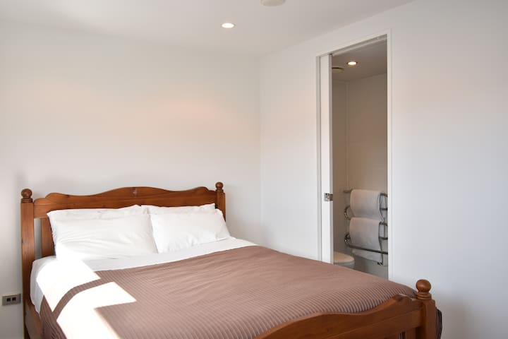Bright and sunny bedroom features a comfortable queen size bed with en-suite bathroom