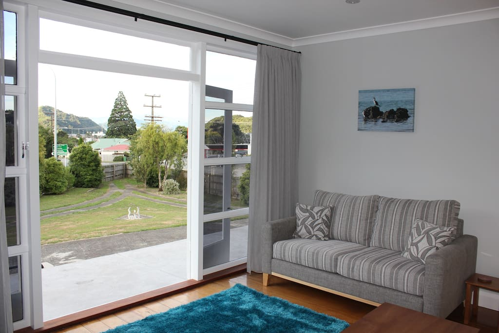 Lounge area opening onto patio and garden areas with distant views of the Marlborough Sounds and Picton Ferry Terminals