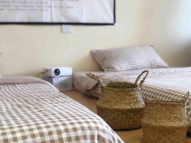 床头配有投影仪,双床可合并成一张大床