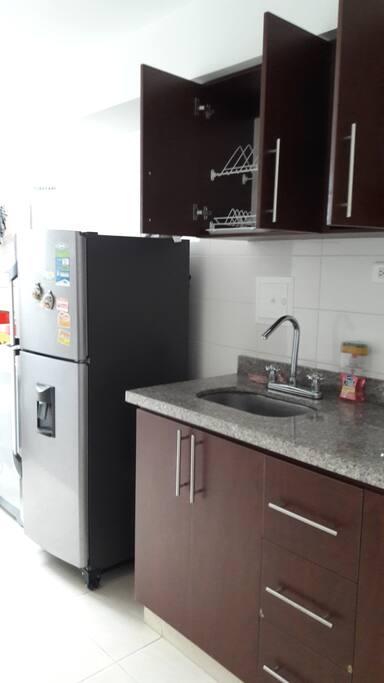 Cocina equipada con utensilios, con nevera, lavadora y colgador de ropa.