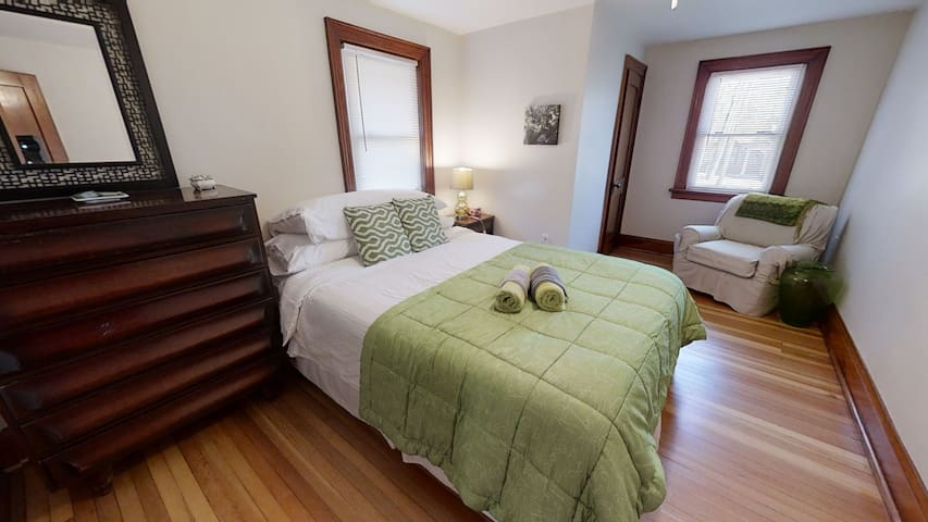 This queen bed  bedroom again features refurnished hardwood floors, closet and two windows and a dresser
