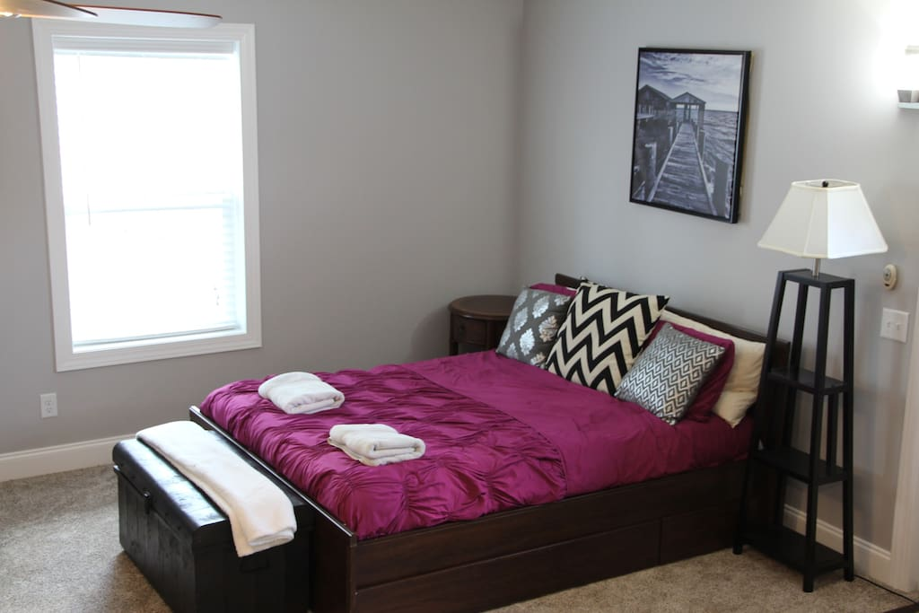 Bedroom area with a lamp, nightstand, and extra blankets