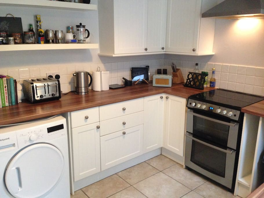 Kitchen with gas oven/grill, fridge freezer, toaster, kettle, iron, washing machine and tumble dryer.