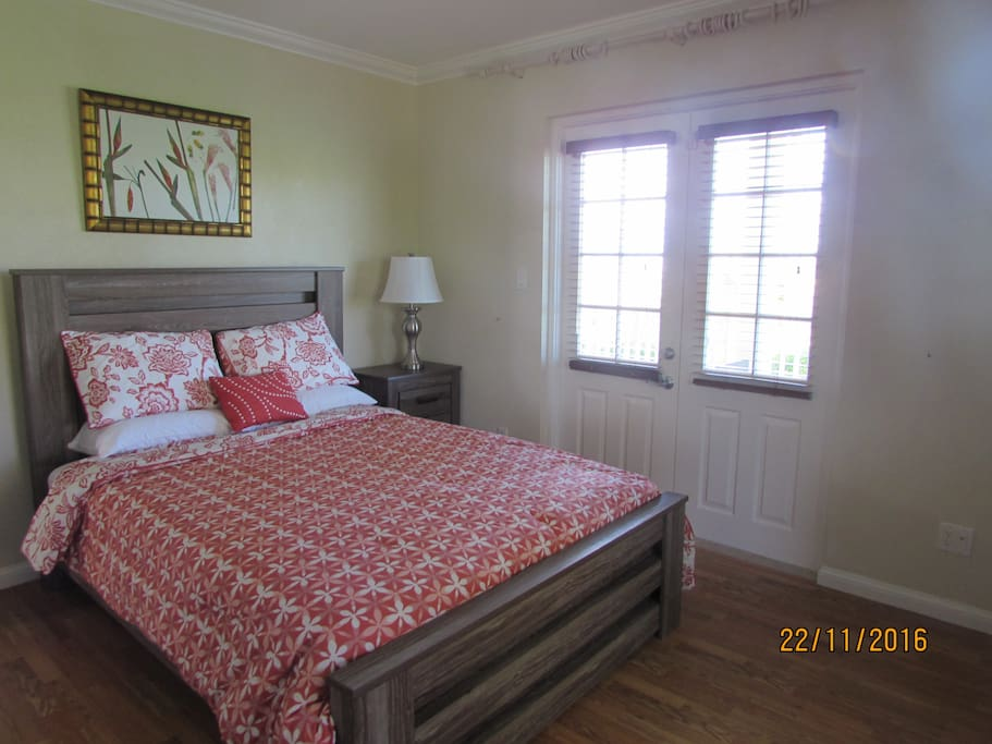 master bedroom with doors out to patio and en suite bathroom (queen bed)