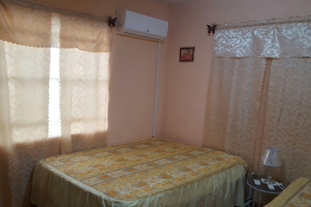 La habitacion con sus dos camas confortables y una mesa de noche con una lampara.Se observa ademas la climatizacion.