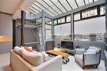 Living   The 36 square meters living room has a large atrium and 2 double glazed bay windows facing courtyard . It is equipped with : dining table for 8 people, sofa, coffee table, cable, TV, armchair, built-in shelves, concrete floor.
