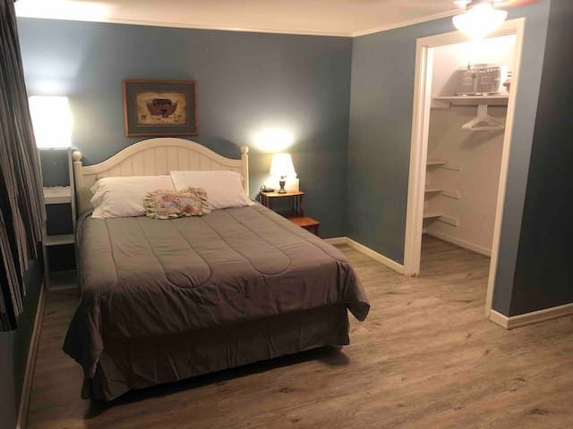 Bedroom with queen bed, charging stations and walk-in closet with extra blanket, hangers and a fan.