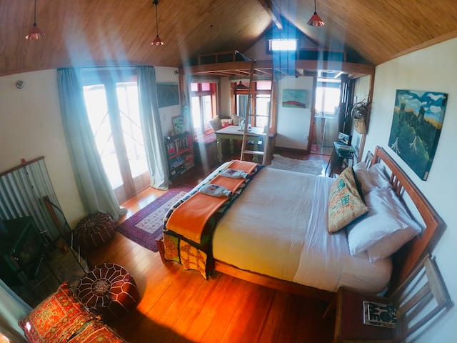 Queen bed with two singles in open loft above.