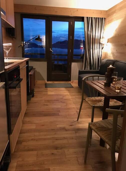 Salon avec canapé convertible et terrasse comprenant une vue sur les pistes et montagnes