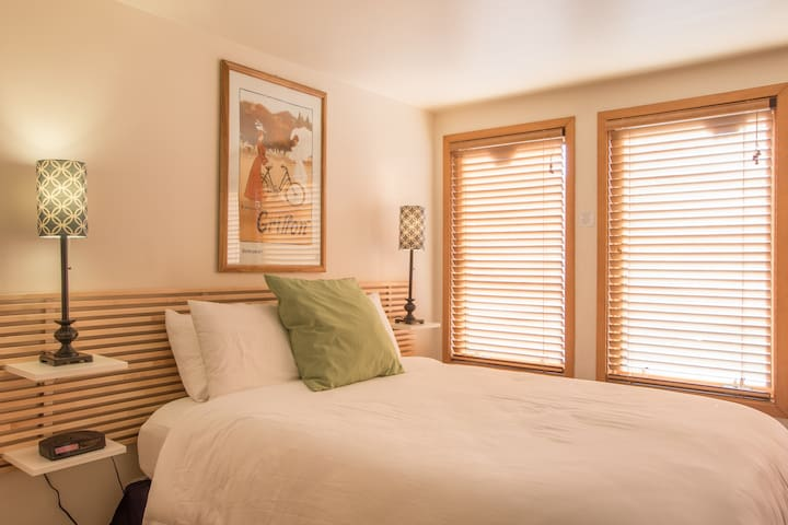 The sunlit bedroom area has a queen-sized bed