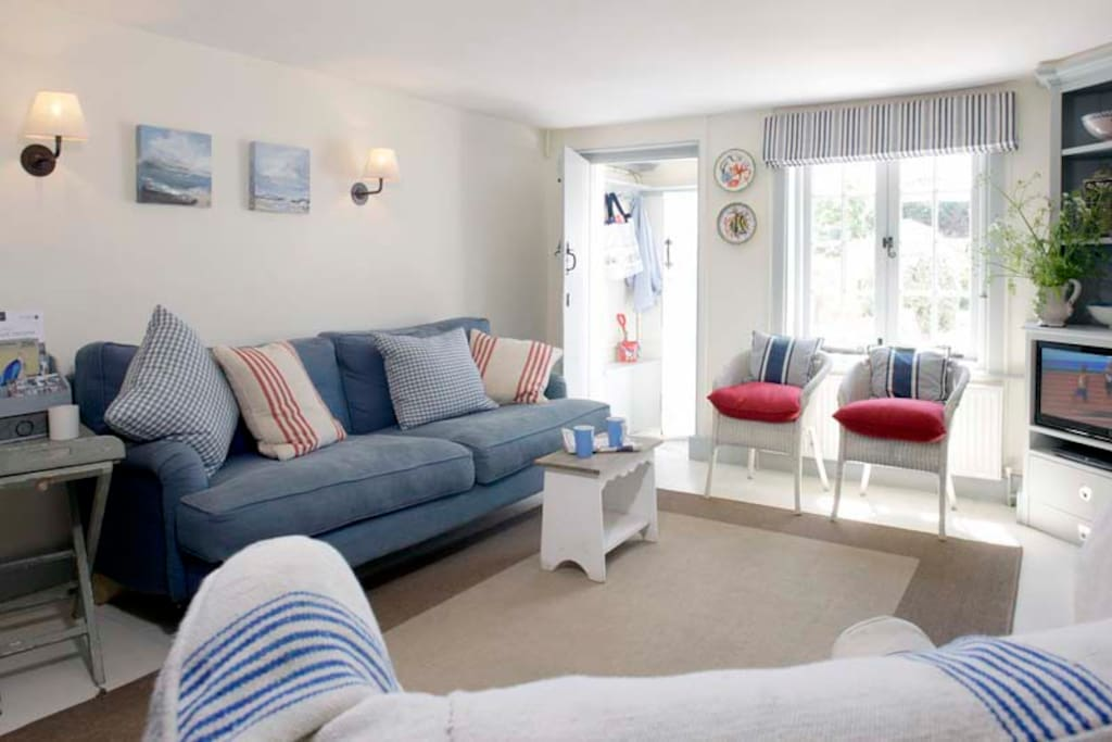 Bright sunny living room over looking the garden towards the sea.