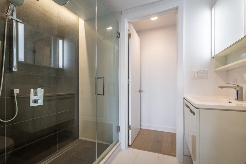 Large walk-in shower with glass door, and rain shower