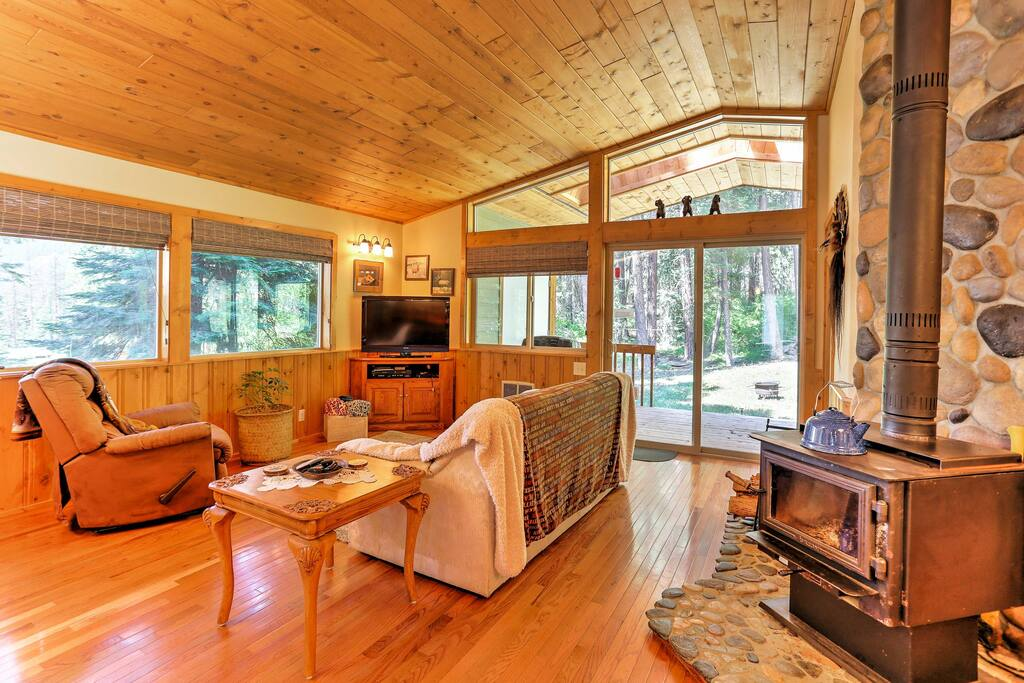The beautiful cabin-style home features pine ceiling and pine trim throughout, along with a wood stove mounted against a beautiful river rock backdrop.