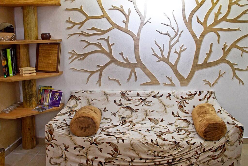 Sillón triple cómodo y librero con amenidades para los huéspedes (guías, libros, juegos de mesa y libro de visitas)