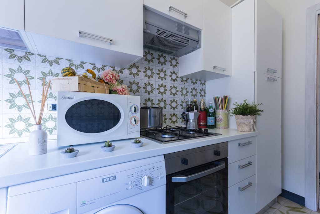 Kitchen with a washing machine, microwave and, hob and stove