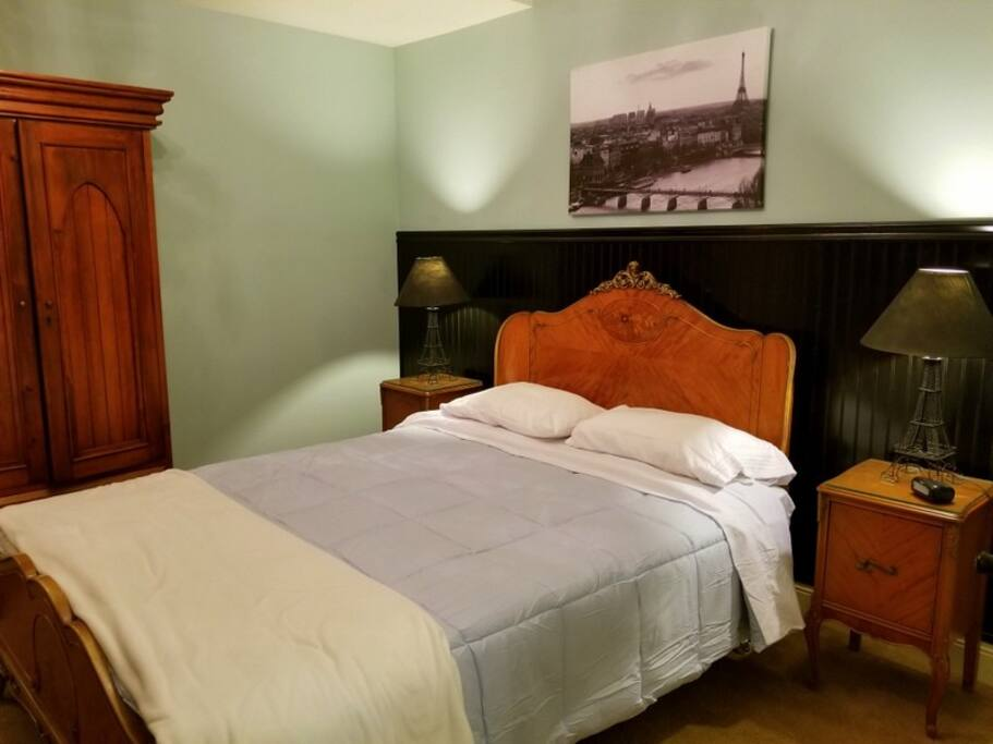 The room is furnished with antiques and features a luxurious queen size bed with matching night stands and Eiffel tower laps.  It is decorated in peaceful soft blue tones.