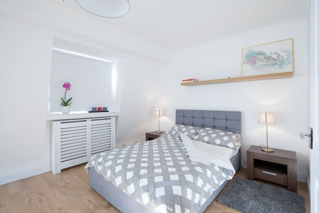 Large bedroom with comfortable bed for 2 people, chest of drawers and storage for beddings.