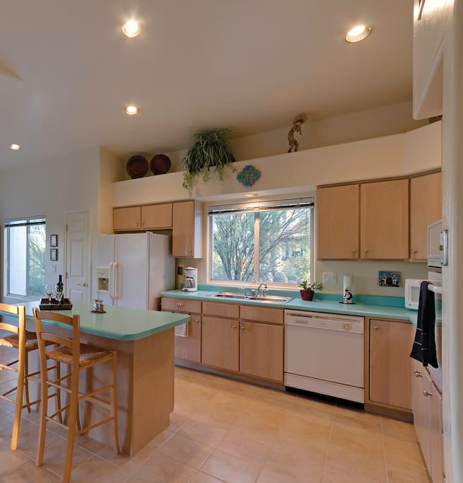 Light and airy kitchen with island. Ceramic tile flooring in all but 2 bedroom