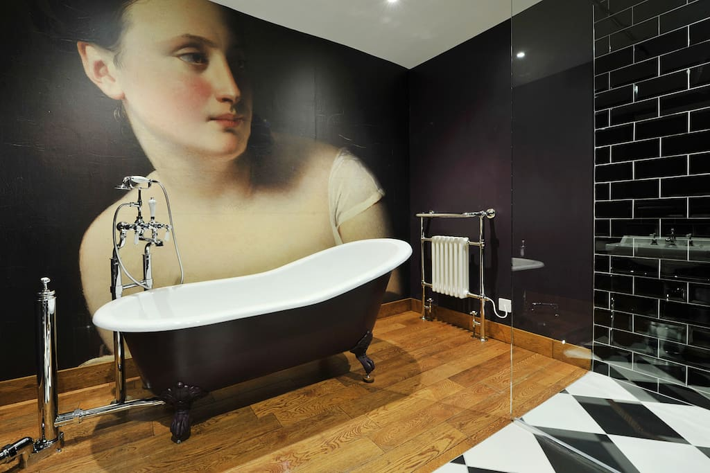 Large walk in shower and feature bath tub with wall mural.