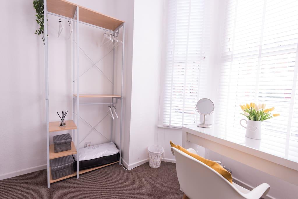 Open wardrobe, desk and hairdryer.
