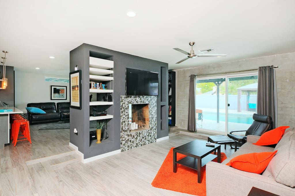 Dual living rooms are separated by a decorative fire place and large flat screen TVs.