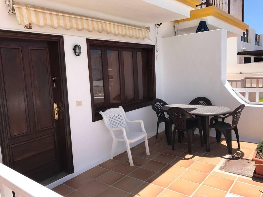 Terraza soleada con toldo, mesa y sillas