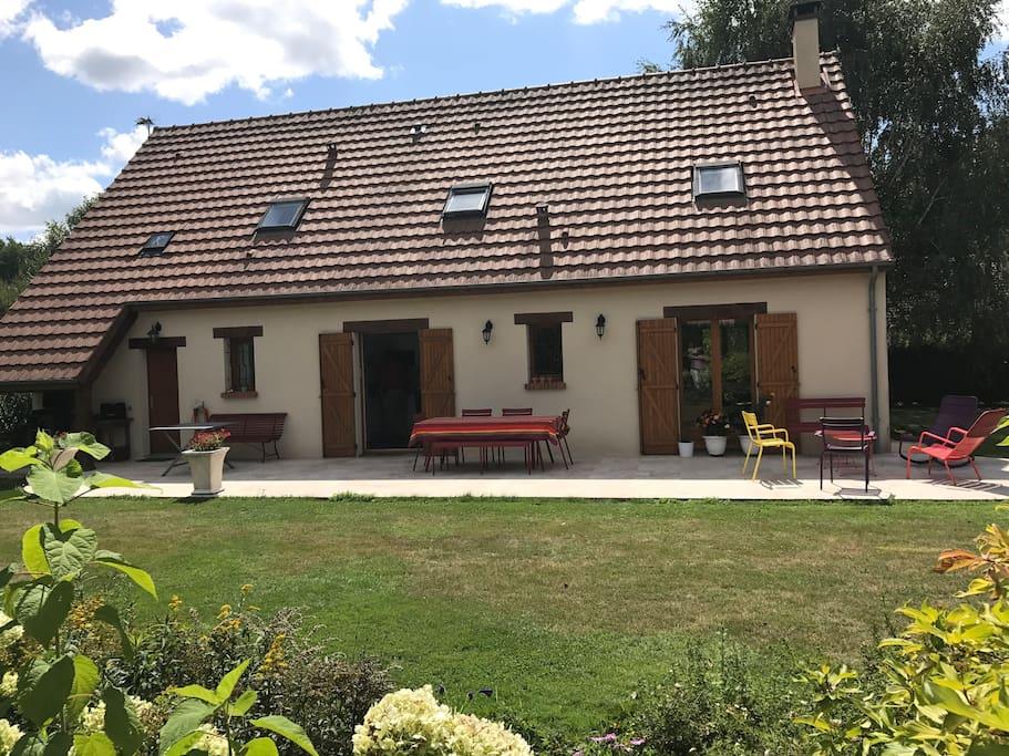L'arrière de la maison avec une grande terrasse face au jardin fleuri et arboré