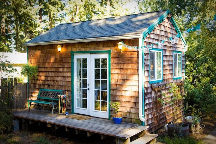 Rustic tiny cabin on backyard farm with goats
