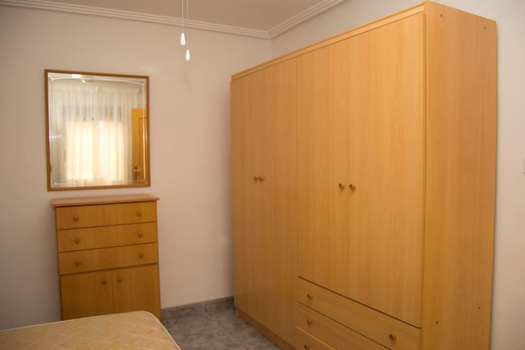 Perspectiva 2 de la habitación con cama de matrimonio. Dos armarios grandes y una cómoda para zapatillas con un espejo y cajones.