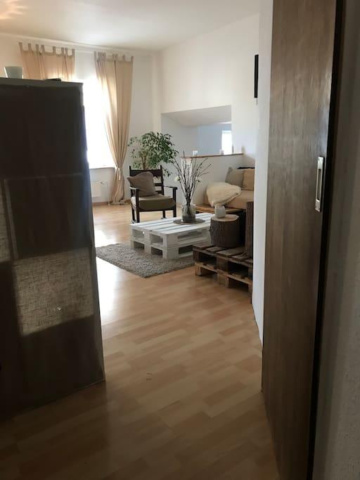 Eingang in die Wohnung, offenes Wohnzimmer und rechts der Eingang zum Schlafzimmer.