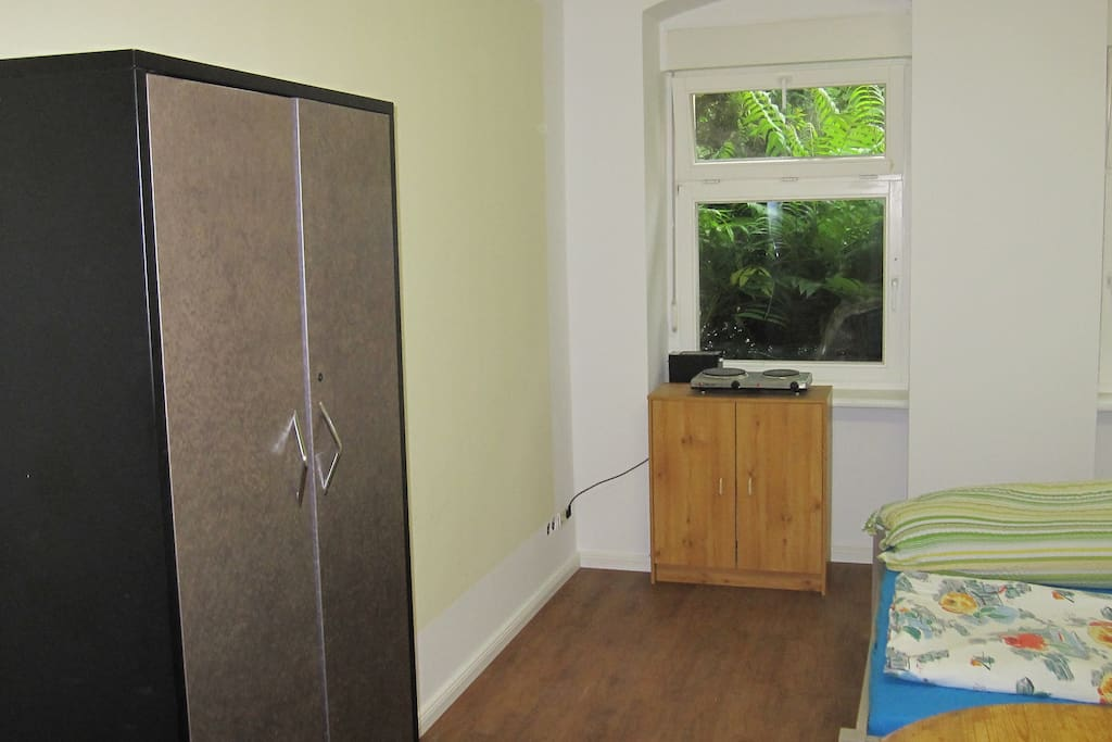 Schlafzimmer (Zi 2), Blick von Tür auf linke Seite des Zimmers mit Kommodenschrank am Fenster, drauf stehend 2 Kochplatten, dahinter 1 Toaster