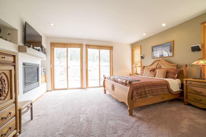 Master Bedroom with King Bed, gas fireplace, flatscreen TV, mini fridge, walk-in closet, bathtub and shower.