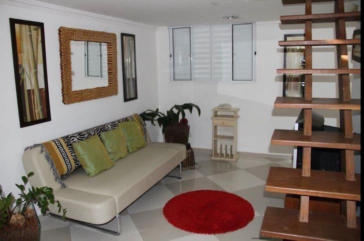 Saleta de entrada do apartamento que tem a escada de madeira que dá acesso ao quarto do mezanino.