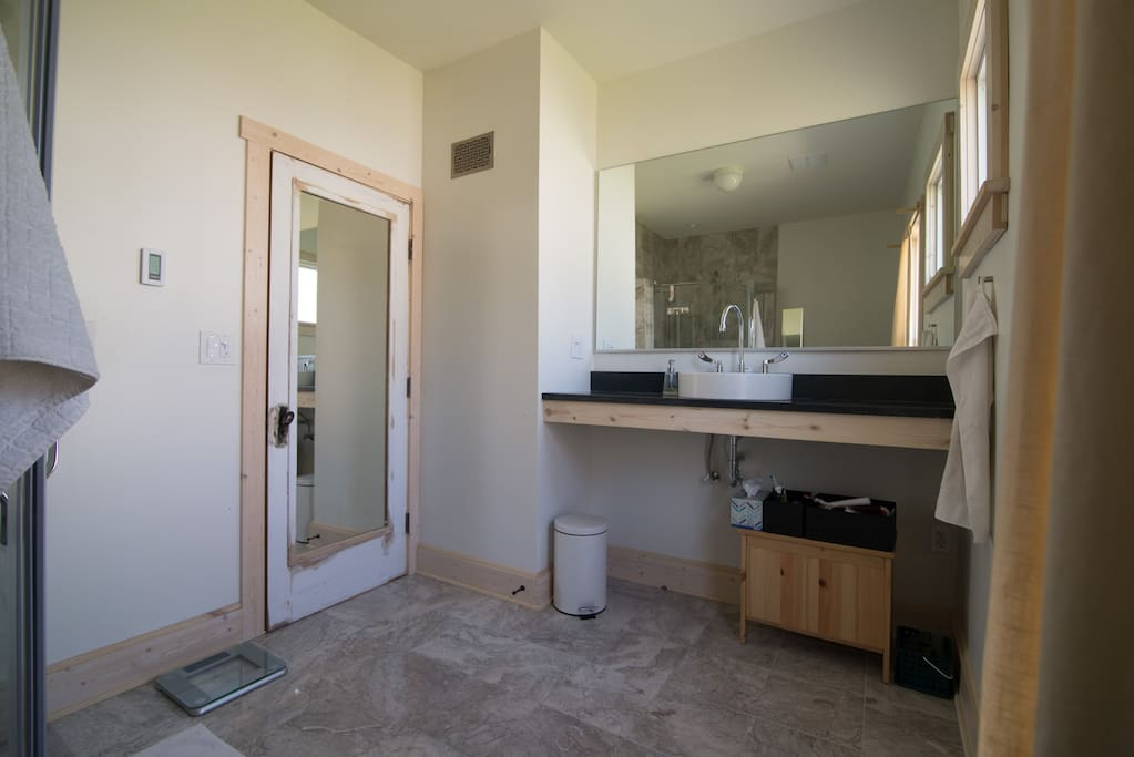 We share this bathroom and it's our sanctuary in the mornings. It features marble floors and a wall-width mirror, and plenty of counter space by the sink. The full-height mirror is integrated into the solid wood door and we have another full height mirror as well. The main window has a privacy curtain and the upper window is frosted.