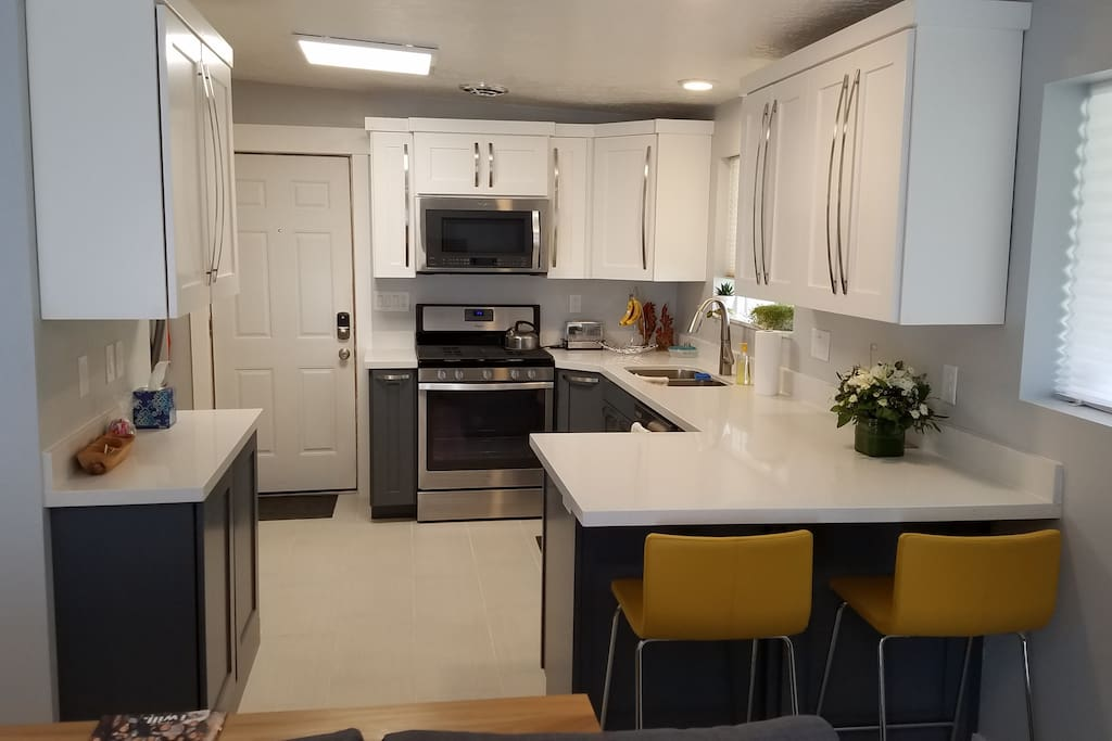 Full kitchen with gas range, dishwasher, fridge, and microwave.