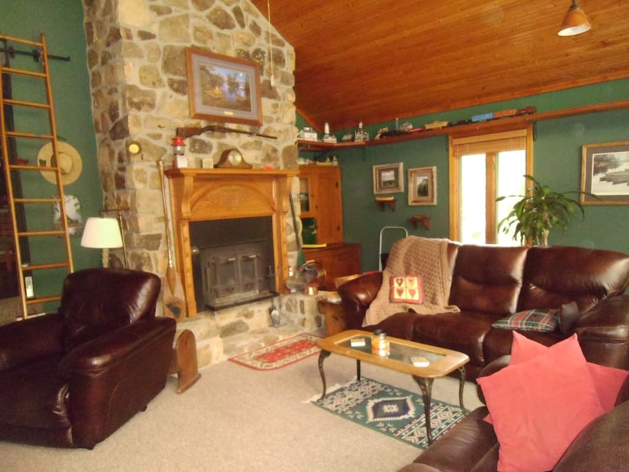 Great Room includes wood fireplace, big screen TV, recliner plus two couches with recliners and walkout to saltwater pool with diving board.