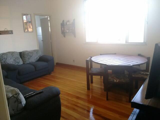 Sala espaçosa com 2 sofás, mesa de jantar grande, rack com TV e janela com vista panorâmica do centro da cidade.