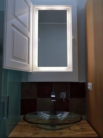 Il lavabo in cristallo sul piano realizzato con gli ulivi del nostro giardino e la finestra originale trasformata in specchio.