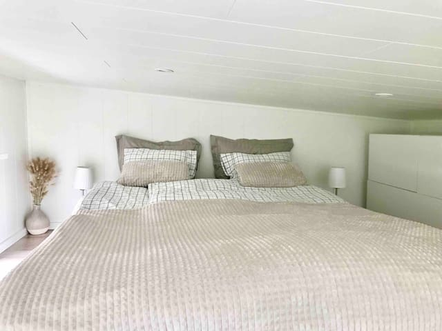 Sleeping loft. Comfortable matress - EU King,  US larger Queen. (160 cm = 63 inch wide, 200 cm = 79 inch long). 2 pillows per person. Thick matress pad + protector (washed between guests). Bedside lamps, window, fan. Open plan towards living area.