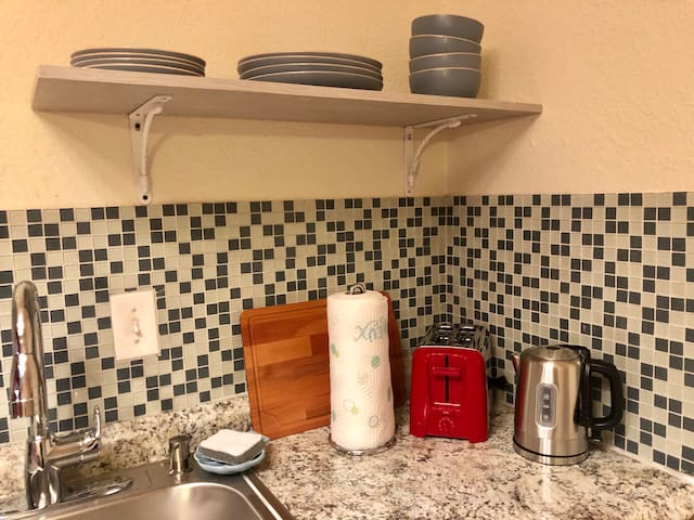 Brand new kitchen appliances (toaster, electric kettle), cutting board, bowls and plates, paper towels, sponge and built in dish washing liquid