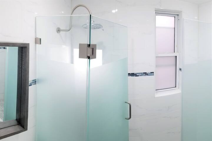 Enjoy the most luxurious shower you've ever taken underneath the best rain shower head in the industry inside a custom-tiled frosted glass-enclosed shower