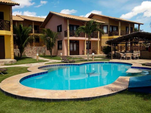 Vista do condomínio com a piscina (com cadeiras e espreguiçadeiras, área de festas (churrasqueira + forno a lenha + cadeiras e mesas + pia + bancada).