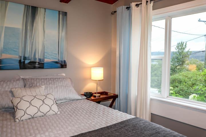 Master bedroom with queen size bed and view of the river.