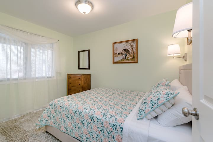 Second queen bedroom with small chest of drawers and closet.