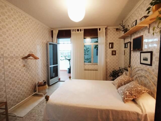 DORMITORIO 4. Habitación con cama doble de 135 cm, con acceso a una soleada galería con vistas a la finca (parte trasera de la casa).